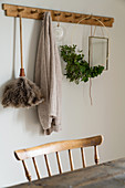 Feather duster, wreath of leaves and cardigan hanging from wooden coat rack