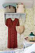 Hat boxes and red dress on wall-mounted coat rack