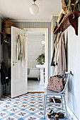Chair below wall-mounted coat rack in hall with tiled floor and view into bathroom