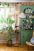 Collection of ceramics in green, glass-fronted cabinet, standard lamp and potted palm in living room