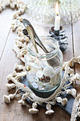 Collection of buttons and antique spoons in jar surrounded by tasselled trim