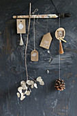 Selbstgemachtes Mobile mit Quasten, Papieranhängern, Zapfen und Silbertalerzweig