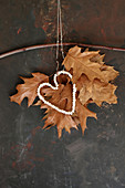 Autumnal arrangement of dried oak leaves with bead heart