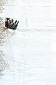Crown on white broderie anglaise tablecloth