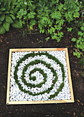 Miniature bed with a spiral of grass and white gravel decorating garden