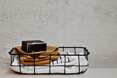 Cloths, knitted cloth and soap in small wire basket