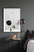 Modern artwork on grey wall above bedside table in bedroom