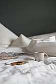 Plate of biscuits, mug, book and glasses on bed with white bed linen
