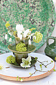 Springlike flower arrangement in green ceramic cups