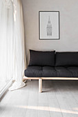 Simple futon sofa with black cushions in corner next to glass wall