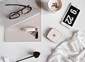 Tasse Kaffee und Handy daneben Buch, Brille und Nachthemd