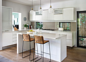 Barstools at counter in modern, white, open-plan kitchen