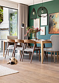 Dog lying on floor in dining room with green wall