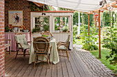 Table and rattan chairs on rustic terrace with awning in garden