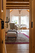 View through open wooden door into cosy, country-house-style living room