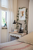 Plant climbing over picture above bedside table in rustic bedroom