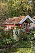 Red summerhouse behind fence in late summer garden