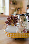 Hydrangea and sugar bowl in yellow tart dish used as tray