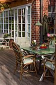 Rattan chair around garden table on terrace of brick house