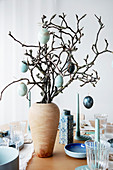 Easter eggs hung from branches in wooden vase on set table