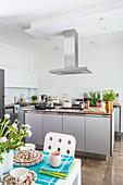 Offene Küche mit grauer Kücheninsel und Edelstahl-Abzugshaube