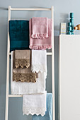 Towels of various colours with fringes and lace trim hung on towel rack