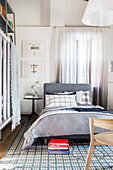 Bed with upholstered headboard and grey bed linen on blue-and-white patterned rug