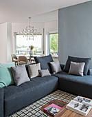 Blue corner sofa on geometric rug in seating area