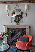 Coral-red easy chair in front of fireplace with decorative metal screen