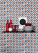 Kitchen utensils on shelf on graphic blue-and-red wallpaper