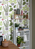 Kitchen utensils and plants on shelves against plant-patterned wallpaper