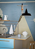 Sink unit with blue front against wall with artistic mural wallpaper