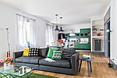 Sofa, dining table and kitchen area in bright, open-plan interior with green and grey accents