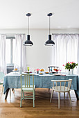 Dining table and chairs of various shapes below industrial pendant lamps