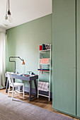 Desk next to stationary on metal ladder in room with mint-green walls