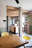 Offener Küchenbereich im Retrostil mit Esstisch, Kücheninsel und Holzbalkendecke