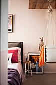 Pale pink walls and cradle hung from ceiling in bedroom