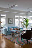 Pale blue sofa in front of large windows in exotic living room