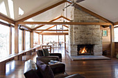 Fireplace under gable ceiling in spacious open-plan interior of modern wooden house