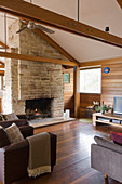Seating area around fireplace in modern wooden house