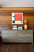 Abstract artwork on rustic wooden wall above grey double chest of drawers