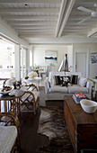 White two-seater sofa and bamboo armchair in beach-house living room