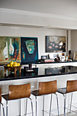 Barstools at breakfast bar of open-plan kitchen decorated with abstract paintings on walls