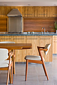 Dining table with upholstered chairs in front of wooden cupboards and wooden back wall
