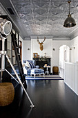 Studio lamp and ladder in open-plan interior with silver stucco ceiling