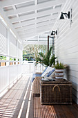Wicker trunk used as table and couch on roofed wooden veranda