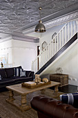 Rustic coffee table and sofa in interior with staircase and silver stucco ceiling