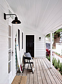 Bench and surfboard on covered porch with white wood paneling
