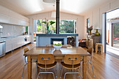 Dining table, chairs and fireplace next to white kitchen counter in open-plan interior