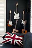 Union-flag cushion on sofa in front of guitars on black wall